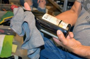 Carlos carefully and thoroughly dusts each bottle with a soft, dry cloth.