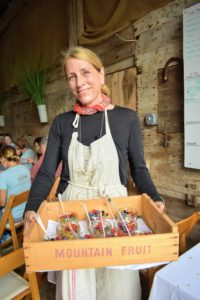 Phoebe Cole-Smith owns Dirt Road Farm. Here she is with a box tray filled with glass containers of homemade yogurt, granola and fresh organic berries.