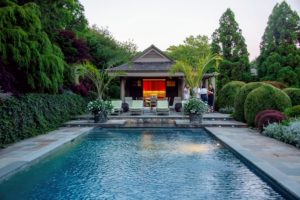 Just off to one side of the home is the pool surrounded by lovely trees and specimen plantings. An intimate seating area can be seen at the far end. (Photo by Daniel Gonzalez for Business of Home)