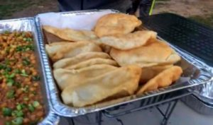 This is called puri, one of the traditional foods in Nepal. It is an unleavened deep-fried bread made with wheat flour and often eaten with the aloo dum, or served as a bread for breakfast.