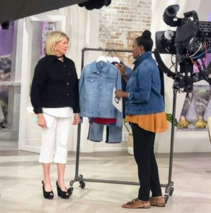 Here I am with QVC host, Jayne Brown. We're looking at my denim jacket in medium indigo. These jackets have a classic fold over collar, long sleeves and two functional pockets. It also comes in a light and dark indigo.