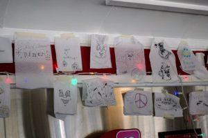 "The diner displays ""Dinah Doodles"" along the wall - showcasing various patron drawings."