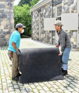 Several hours later, once the stable floors and mats are completely dry, the mats are brought back in and assembled. These mats are very, very heavy – each large piece is at least 250-pounds.