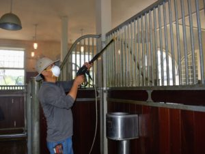 Next, Dawa begins power washing every metal bar of every stall.