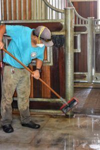 While Phurba uses a sponge broom to scrub the walls, doors and upright stall supports.