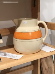 Here is another early Roseville piece - it is about 18-inches in diameter at its widest point and approximately six and a half inches tall. The pitcher is cream color with a one and a quarter-inch orange stripe all the way around.