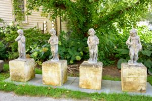 Along the driveway are several ornamental garden statues. This is a set of four lead figures, each representing a different season, raised on large plinth blocks of limestone. They were once part of Oprah Winfrey's personal collection.