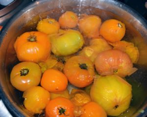 Sanu boils and cools another batch – these are yellow and orange tomatoes. This method is very helpful when working with another person, so one can poach the tomatoes while the second person peels them.