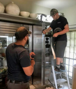 Here, Scott and his apprentice, Julio Ramos, re-insulate the fan cabinet. Re-insulating the cabinet helps prevent warm, moist air from coming into contact with any cold surfaces.