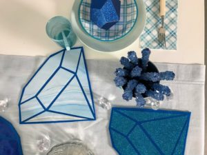 The gemstone placemat decorations can be used to create the table centerpiece. These were done using our patterned premium vinyl and glittered Cricut surfaces.
