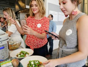 Here, attendees captured photos of the lentil and arugula salad. (Photo by Laura Manzano)