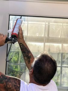 To prevent leaks, Ira caulks and seals the glass with black silicone.