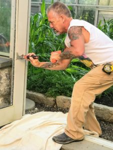 """Ira Heim, from Kuritzky Glass Company, starts by carefully removing the broken pane. Here he is using a """"5-in-one tool"""" designed for working with glass and other similar tasks."""