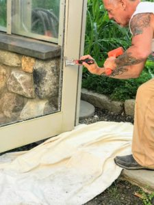 This must be done carefully, so the remaining pane is not damaged in the process. Moldings are on all four sides of the glass, so Ira works his way clockwise around the door.