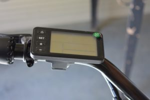 On the left side of the handlebars is an LCD display with a USB charger port for a phone.