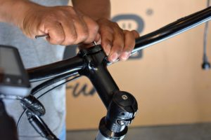 Pete aligns the handlebars with the front wheel and tightens all the necessary bolts.