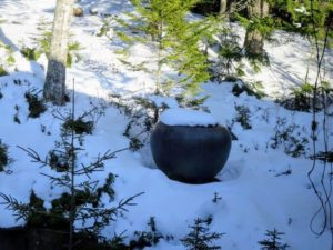 The giant copper urn in the woods is also capped with snow.
