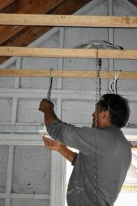 Then he secures the chain to the wooden cross bar in the coop. These heaters are not heavy - just a few pounds. And, because it swings, birds will be less apt to perch on it.