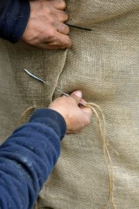 Chhewang works on the other container. We have already had one snow storm hit the area, so it is important to get everything covered quickly. Once the burlap is secured underneath, Chhewang stitches the fabric together, pulling the burlap snug as he goes.