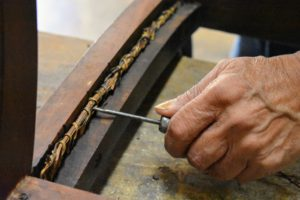 Some of the side binding strands are removed with an awl.