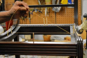 There are six main steps to hand-caning a chair. Danny uses hole-to-hole traditional hand caning, which is weaving individual strips through a series of holes around the perimeter of the chair frame. Danny marks the center holes and draws two horizontal strands of cane as his guide.