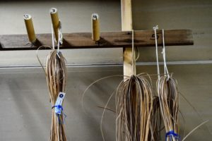 The artisans at Yorkville hang different sizes of rattan chair cane on hooks inside the shop.
