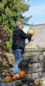 Fernando helps with all the outdoor decorating. Here he is putting a pumpkin on top of one of the front stone columns.