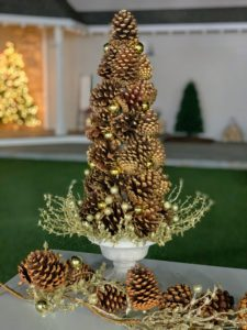 This pinecone topiary is about 24-inches tall and looks so full and festive. This topiary is accented by pinecones, ornaments, and glittered leaf and berry branches.