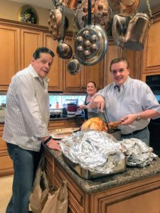 Here, Samantha's father-in-law, Vincent, and his brother Robert, carve the turkey while their sister, Barbara, prepares the gravy.
