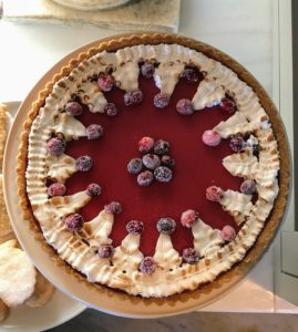 This is a cranberry curd tart. We made the crust using saltine crackers and adorned it with meringue and sugared berries.