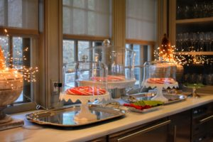 Between my small dining room and my kitchen is the servery - a room from which meals are served. Whenever I entertain, I like to use this area for serving desserts and drinks. On this side, we decorated the counter with giant circular candy canes under the glass domes of these cake stands.