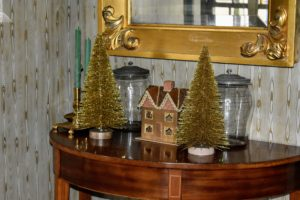 I have two antique demilune tables in my foyer. This one is adorned with more gold Christmas trees and a whimsical village house.