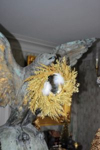 The giant falcon in my entrance hall is among the first things guests see when they visit my home. This year, we placed a cheerful gold wreath and birds in its beak.