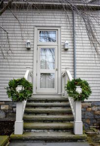 Two wreaths hang at the bottom of the stairs to my Winter House. These wreaths are just resting on the newel posts. Outdoor decorating can be so easy.