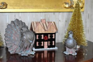 Another house sits on the matching demilune table - flanked by two dove figurines.