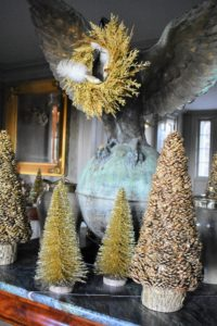 Several gold Christmas trees are gathered around its feet on my green marble table.