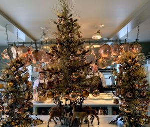 In the kitchen, Chef Pierre and his sous chef, Kevin, prepare the final details of the day's lunch. You can see them waiting for guests to arrive behind this beautiful trio of holiday trees.