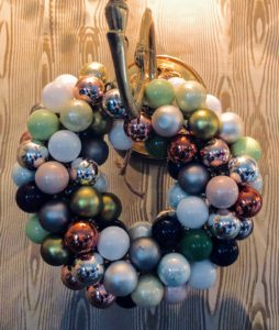 This is one of two nearby sconces decorated with festive Christmas ball wreaths in a variety of pleasant metallic colors.