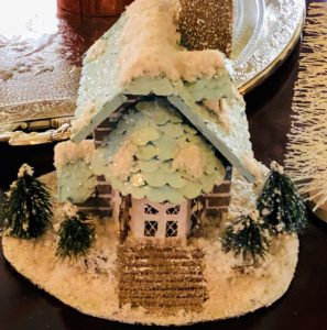 On the dining table is a snow covered village house - surrounded by even more trees.