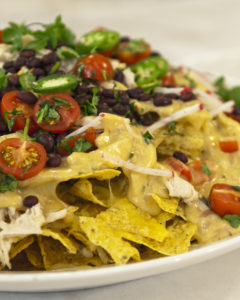 Nachos can be better-for-you, but still decadent! Chef Emeril Lagasse's Nachos Supremo are just as delicious with shredded, skinless, boneless chicken breasts and a fresh black bean and radish salsa.