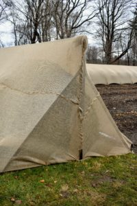 Once completely wrapped, the burlap is pulled tightly against the frame and hand-sewn closed.