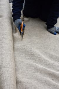 The area being covered is carefully measured, so the burlap pieces can be cut to size.