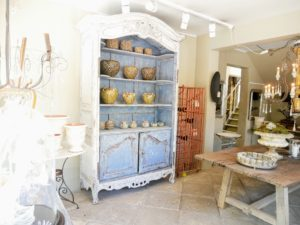 Through the window, we could see this gorgeous French antique hutch and various pieces of pottery and other furniture.
