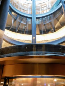 The lift is made of glass and surrounded by a spiral staircase.