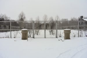 On this side of the cutting garden is a pair of stately Kenneth Lynch garden urns covered in burlap for the winter. The flower garden and the surrounding beds are all covered in a blanket of white.