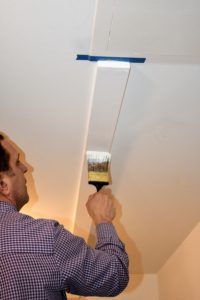 Here he is painting the wood support white - the entire basement is painted white to keep as bright as possible.