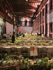 The event was held in Brooklyn, New York at Pioneer Works, owned by artist, Dustin Yellin. The three-story red brick building was built in 1866 for what was then Pioneer Iron Works. The factory, which manufactured railroad tracks and other large-scale machinery, was a local landmark. Guests were invited to sit at long tables set up in rows to maximize conversation.