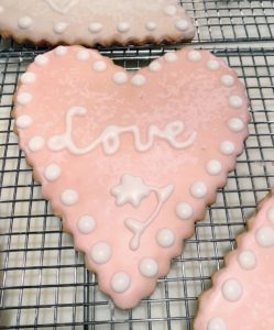 "On this cookie, I wrote ""love"" in script and added both dots and a flower."