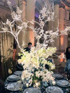 This centerpiece, with its creative use of bright white branches rising up from the white flowers, was presented by Lewis Miller Design. https://lewismillerdesign.com/