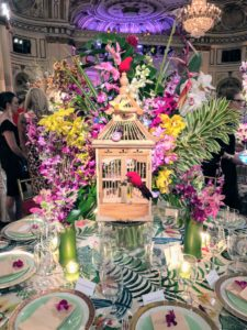 This colorful table centerpiece of flowers surrounding a decorative bird cage was created by the interior design company, Paris Forino. https://parisforino.com/